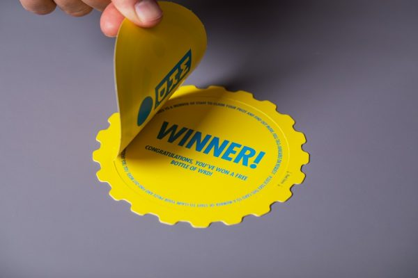 Die cut peel and reveal printing with unique prize message